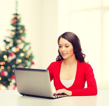 work from home: christmas, x-mas, electronics, gadget concept - smiling woman in red clothes with laptop computer