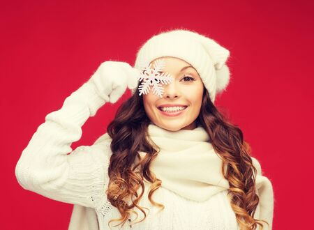 seasonal clothes: winter, people, happiness concept - woman in hat, muffler and gloves with big snowflake Stock Photo
