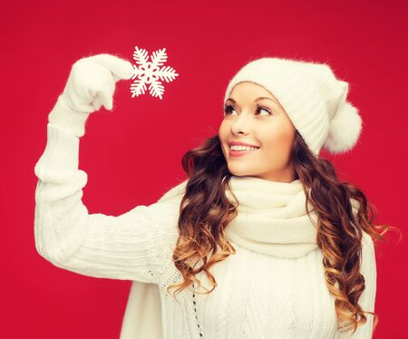 red scarf: winter, people, happiness concept - woman in hat, muffler and gloves with big snowflake Stock Photo