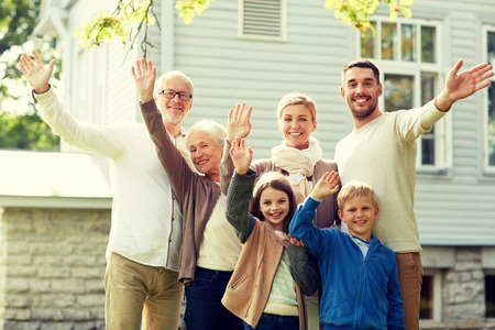 the outdoors: gesture, happiness, generation, home and people concept - happy family waving hands in front of house outdoors