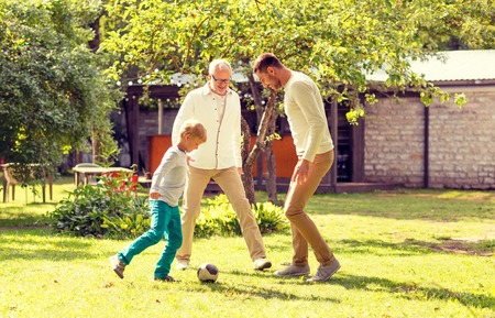 boys playing: family, happiness, generation, home and people concept - happy family playing football in front of house outdoors Stock Photo
