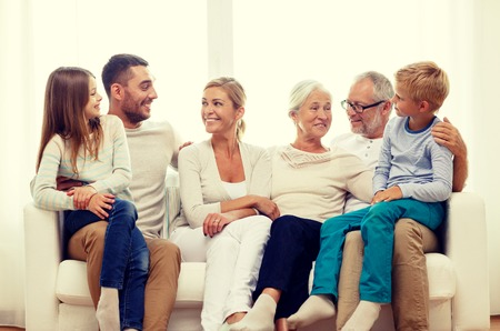old: family, happiness, generation and people concept - happy family sitting on couch at home