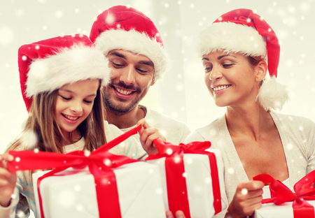 family, happiness, generation, holidays and people concept - happy family in santa helper hats with gift boxes sitting on couch at home Stock Photo