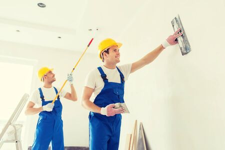 contractors: business, building, teamwork and people concept - group of smiling builders in hardhats with plastering tools indoors Stock Photo