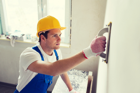worker construction: business, building, profession and people concept - builder with grinding tool indoors Stock Photo