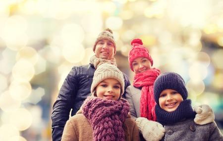 ropa de invierno: la familia, la infancia, la temporada, vacaciones y la gente - concepto de familia feliz en ropa de invierno sobre fondo de las luces