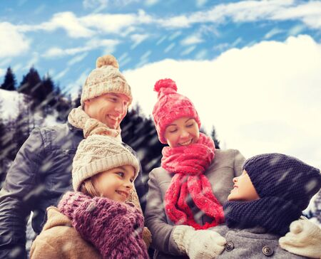 mujer hijos: la familia, la infancia, la temporada y la gente concepto - familia feliz en ropa de invierno más de fondo cubierto de nieve las montañas