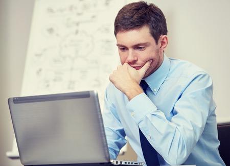 Negocio, la gente y el concepto de trabajo - hombre de negocios sentado con el ordenador portátil en la oficina delante de la pizarra Foto de archivo - 47737007