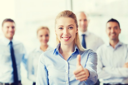 thumbs up: business, people, gesture and teamwork concept - smiling businesswoman showing thumbs up with group of businesspeople in office