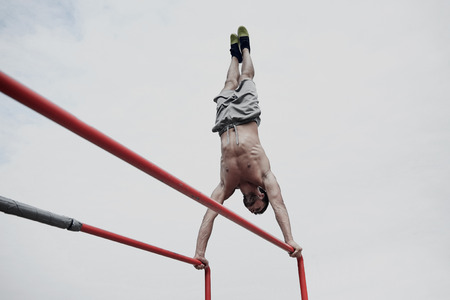 calisthenics: fitness, sport, training and lifestyle concept - young man exercising on parallel bars outdoors