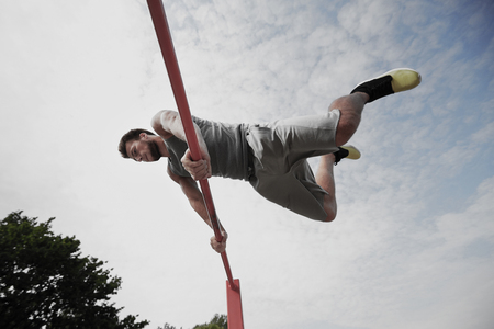 calisthenics: fitness, sport, training and lifestyle concept - young man exercising on horizontal bar outdoors