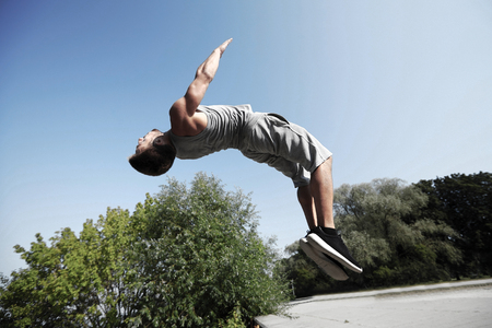 fitness, sport, parkour and people concept - young man jumping in summer park Фото со стока