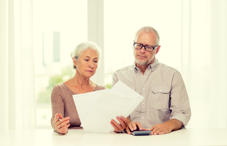 business savings: family, business, savings, age and people concept - senior couple with papers and calculator at home