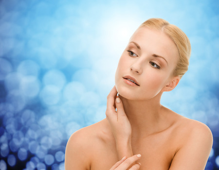woman neck: beauty, people and health concept - beautiful young woman touching her neck over blue lights background
