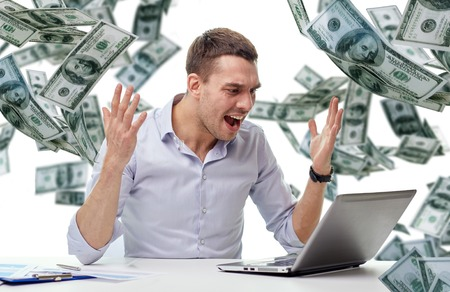 money issues: business, people, stress, fail and technology concept - angry businessman with laptop computer and papers shouting over falling money background