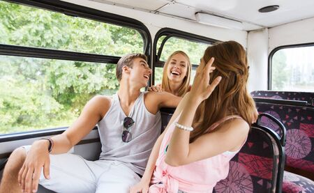 friends happy: friendship, travel, vacation, summer and people concept - group of happy teenage friends traveling by bus and laughing Stock Photo