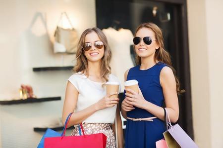 chicas de compras: venta, el consumismo y el concepto de la gente - las mujeres jóvenes felices con bolsas de la compra y vasos de papel café en escaparate en la ciudad