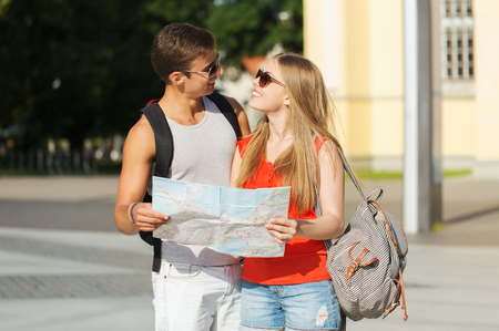 rucksack ': travel, tourism, summer vacation and people concept - smiling couple with map and backpack looking for location in city