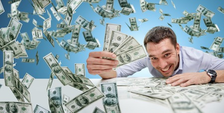 business, people, success and fortune concept - happy businessman with heap of dollar money over blue background Stock Photo
