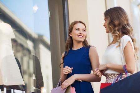 personas en la calle: venta, el consumismo y el concepto de la gente - las mujeres jóvenes felices con bolsas de la compra hablando en al escaparate en la ciudad Foto de archivo