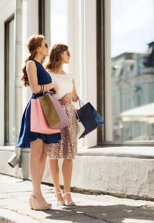 shopping: bán, tiêu thụ và người khái niệm - phụ nữ trẻ hạnh phúc với túi mua sắm nhìn vào cửa sổ cửa hàng trong thành phố