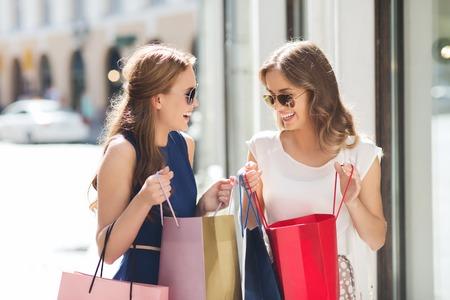 shopping: la venta, el consumo y el concepto de las personas - mujeres jóvenes felices con bolsas de la compra hablando en la ventana de la tienda en la ciudad Foto de archivo