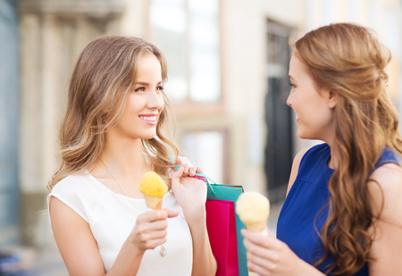 ice cream woman: sale, consumerism, summer and people concept - happy young women with shopping bags and ice cream talking on city street Stock Photo