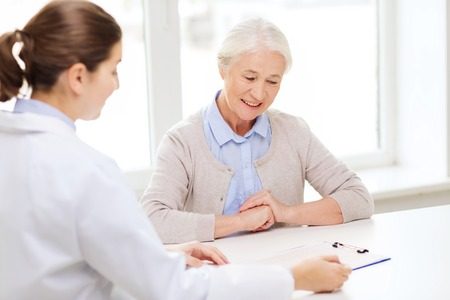 recetas medicas: la medicina, la edad, la salud y las personas concepto - doctor con portapapeles y reuni�n mujer mayor en el hospital