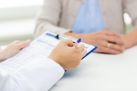 exam room: medicine, age, health care and people concept - close up of senior woman and doctor hands with clipboard meeting in medical office Stock Photo