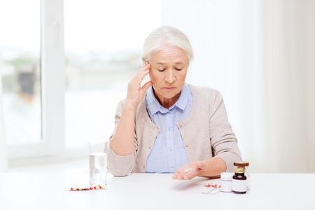 ヘルスケア: 年齢、医学、医療、人々 コンセプト - 薬、家庭での水のガラスで年配の女性