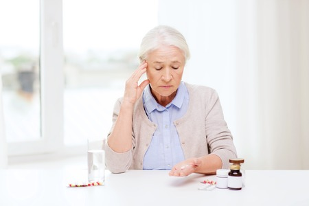 age, medicine, health care and people concept - senior woman with pills and glass of water at home Imagens