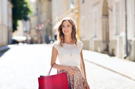 Verkauf, Konsum und Menschen Konzept - glückliche junge Frau mit Einkaufstüten entlang Stadt Straße