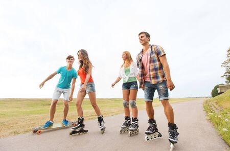rollerblading: summer holidays, leisure, sport, love and people concept - group of happy teenage friends with rollerskates and longboards