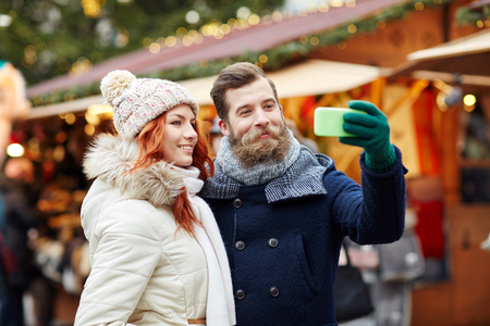 holidays, winter, christmas, technology and people concept - happy couple of tourists in warm clothes taking selfie with smartphone in old town Stock Photo