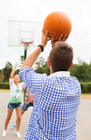 teenage guy: summer vacation, sport, games and friendship concept - group of happy teenagers playing basketball outdoors from back