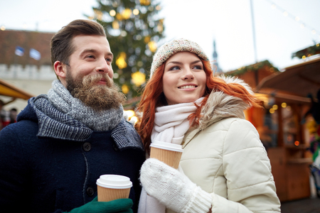hot drink: holidays, winter, christmas, hot drinks and people concept - happy couple of tourists in warm clothes drinking coffee from disposable paper cups in old town