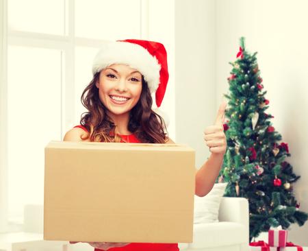sala parto: Natale, vacanze invernali, la consegna, il gesto e la gente concept - donna sorridente in cappello della Santa con cassetta dei pacchi che mostra i pollici in su sopra soggiorno con albero di Natale sfondo Archivio Fotografico