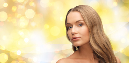 beauty, people, hair care, holidays and health concept - beautiful young woman face over yellow lights background