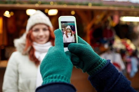 tourists: holidays, winter, christmas, technology and people concept - happy couple of tourists in warm clothes taking picture with smartphone in old town