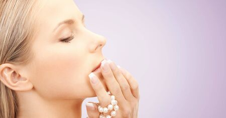 beauty face: beauty, luxury, people, advertisement and jewelry concept - face of beautiful woman with sea pearls beads in hand over violet background Stock Photo