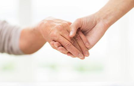 manos entrelazadas: las personas, la edad, la familia, la atención y el apoyo concepto - cerca de la mujer mayor y una mujer sosteniendo jóvenes manos