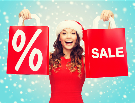shopping, sale, gifts, christmas, x-mas concept - smiling woman in red dress and santa helper hat with shopping bags Stock Photo