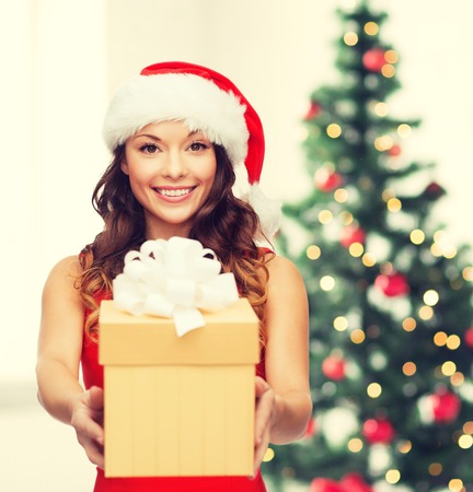 christmas party: christmas, x-mas, winter, happiness concept - smiling woman in santa helper hat with gift box