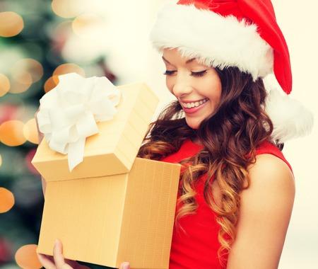 クリスマス、クリスマス、冬、幸せコンセプト - ギフト ボックス付きサンタ クロース ヘルパー帽子の女性を笑顔