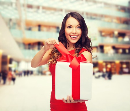 navidad elegante: navidad, días de fiesta, día de San Valentín, celebración y la gente concepto - mujer sonriente en vestido rojo con caja de regalo sobre fondo de centro comercial