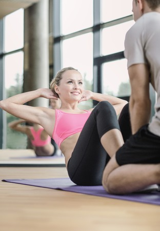 fitness gym: sport, fitness, lifestyle and people concept - smiling woman with male personal trainer exercising in gym