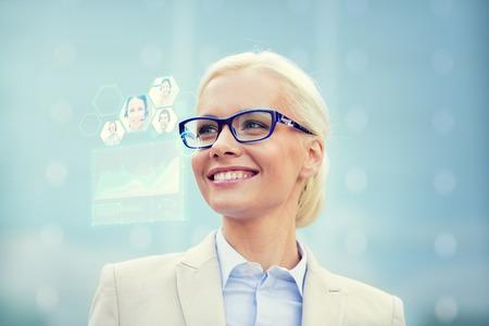 comunicazione: affari, persone, tecnologia del futuro e il concetto di comunicazione - giovane imprenditrice sorridente in occhiali con schermo virtuale, chat video e grafici di proiezione all'aperto Archivio Fotografico
