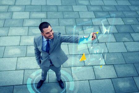 tecnologia informacion: empresarial, el desarrollo, la tecnolog�a y las personas y concepto - joven empresario sonriente apuntando con el dedo a las pantallas virtuales con gr�ficos en exteriores de arriba