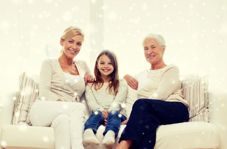 grandmother and children: family, happiness, generation and people concept - smiling mother, daughter and grandmother sitting on couch at home