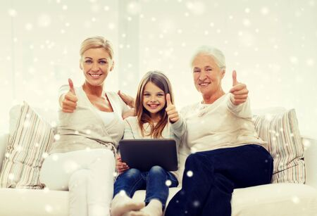 computer generation: family, generation, technology and people concept - smiling mother, daughter and grandmother with tablet pc computer sitting on couch and showing thumbs up gesture at home Stock Photo